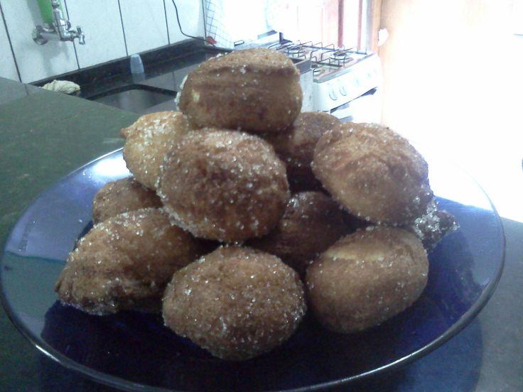 1 ovo - 5 a 6 colheres (sopa) de açúcar - 1 xícara de leite - 2 e 1/2 xícaras de farinha de trigo - 2 colheres (chá) de fermento em pó - Canela e açúcar para polvilhar - Óleo para fritar - Raspas de limão e canela (opcional) -