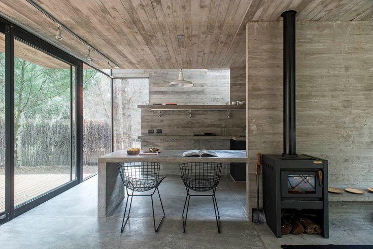 Бетонная барная стойка-обеденный стол разделяет кухню и гостиную. .