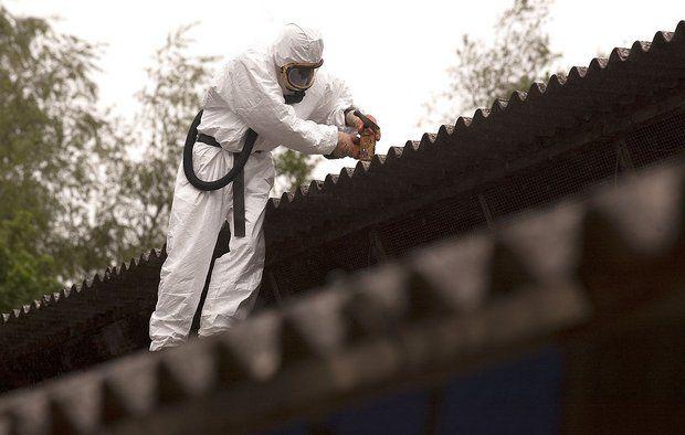 mand i beskyttelsesdragt fjerner asbest fra tag