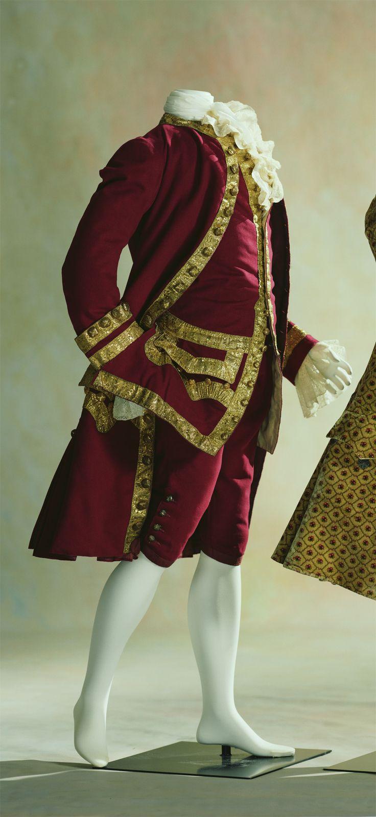(chaqueta, chaleco y pantalón)1750-60-Inglaterra  Material:Vino de color rojo de lana, abrigo, chaleco adornado con galones de oro y los botones envueltos con hilos de oro, chaleco de manga.  Un conjunto de chaqueta, chaleco y pantalones que representan el traje típico usado por los hombres durante el siglo 18.