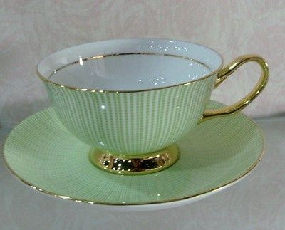 Green and gold tea cup and saucer.