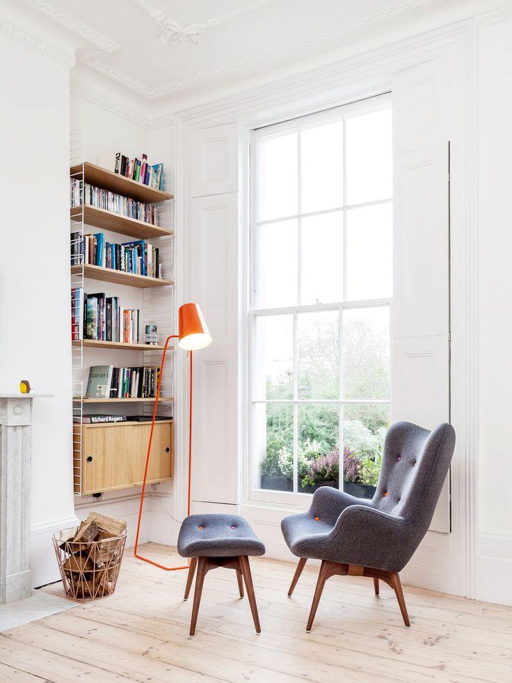 Reading corner with small bookshelf, orange, industrial floor lamp and midcentury grey armchair