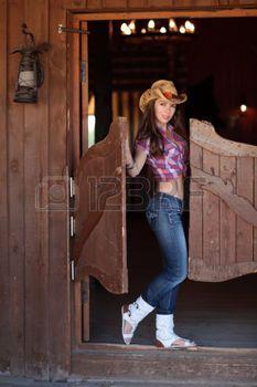 saloon western: Une jeune femme dans des vêtements de cow-boy debout dans l'embrasure de la salle