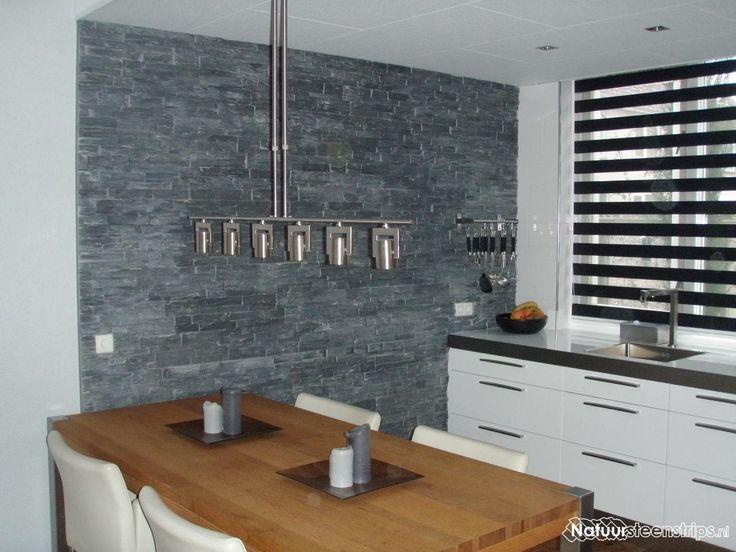 Zwarte lei natuursteenstrips verwerkt in de keuken, decoratieve wandbekleding van natuursteen.