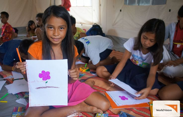 Jinky from the #Philippines shows her #drawing of a #flower. Her school was destroyed during Typhoon Haiyan, so #WorldVision provided space and supplies for children to #play and #learn. Photo by Crislyn Joy Felisilda, World Vision