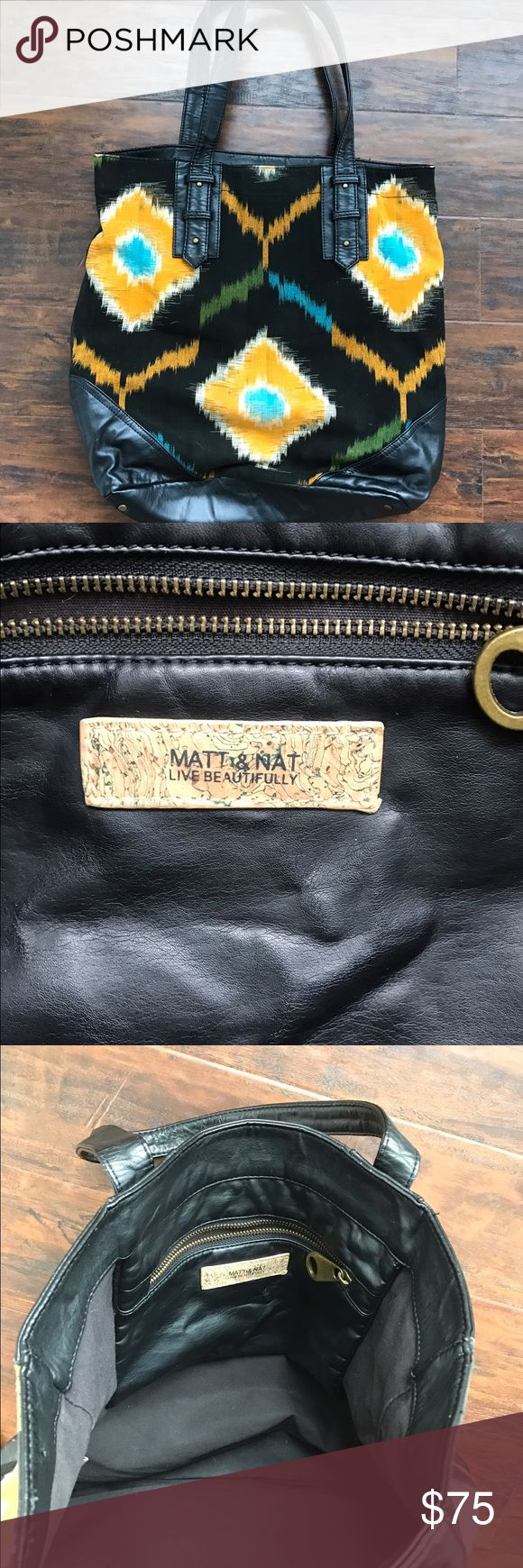 Matt and Nat Zocalo Tote Used. This wrinkled faux-leather tote features a print canvas front panel. Lined interior features zip pocket. Lining is made of recycled plastic bottles. Matt and Nat Bags Totes