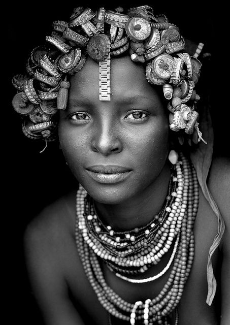 Daasanach tribe girl - Omorate Ethiopia - Creativity to make a headdress with Cola & beer caps, a wrist watch band. Sublime elegance in her pose. She is a jewel.