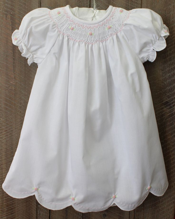 Beautiful take home outfit for baby girl. Sweet smocked daygown with scalloped hem and pink roses. Shop our baby boutique online for classic baby clothing and gifts.(https://www.hiccupschildrensboutique.com/infant-girls-white-smocked-daygown-rosalina/)