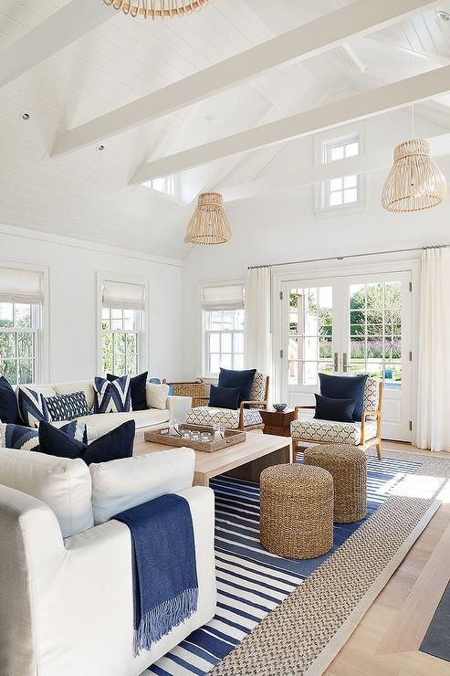 The ceiling but wood. White and blue cottage living room features white slipcovered sofas adorned with blue pillows and blue fringe throw blankets facing a blond wood waterfall cocktail table placed atop a blue striped rug layered atop a gray bound sisal rug.