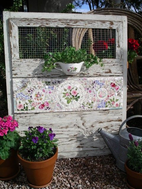 Wooden Garden Gate with a Mosaic Panel and Teapot Planter. Love this combination and flower theme. For more DIY creative planter ideas see http://themicrogardener.com/6-easy-diy-container-garden-projects/ | The Micro Gardener