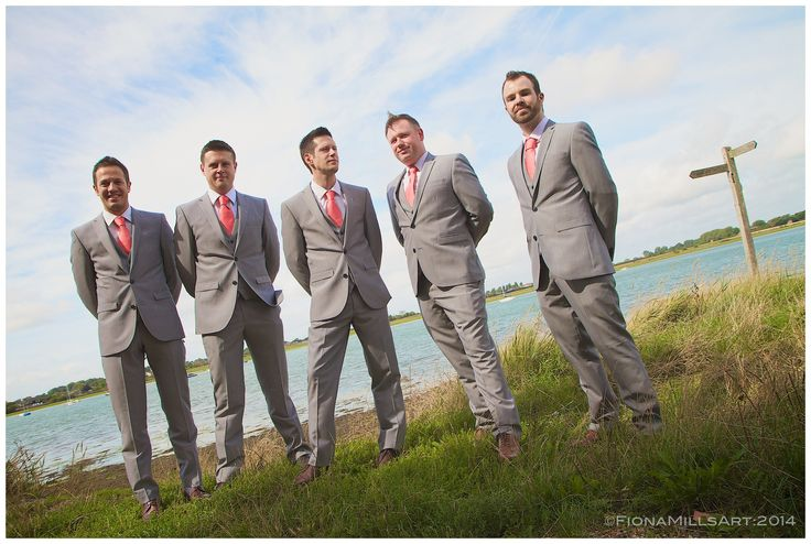 Groomsmen. Groom, best man and ushers pose for a creative portrait in Bosham, West Sussex. Style: grey suits, white shirts, coral tie, brown shoes. Blue sky, wispy clouds. Wedding photograph ideas. Creative and artistic weddings photography by: www.fionamillsart.com