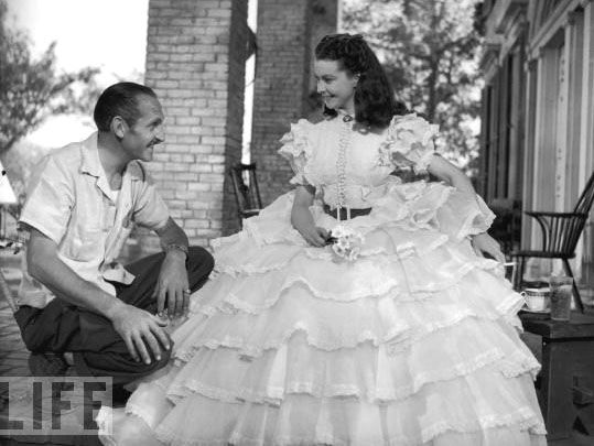 """Costume designer Walter Plunkett with Vivien Leigh in the 'Barbecue dress' on the set of """"Gone with the Wind"""", 1939"""