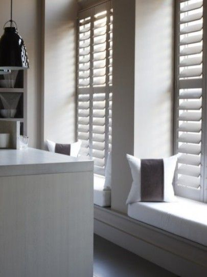Window seat. Tall window full height plantation shutters in soft white with…
