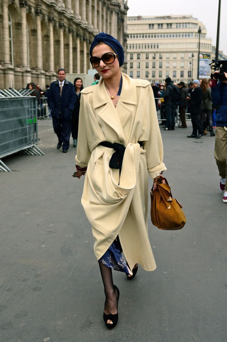 This bird of paradise is the Parisian stylistCatherine Baba. Her look is eccentric, colorful and very retro. I like the contrast combination of dark blue silk dress with floral patterns and pastel yellow coat and the choice of accessories. What can we learn from Catherine Baba: How to drape the perfect turban and to bike with sky-high Louboutins.