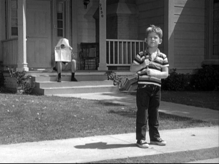Opie walking to school under Barney's watchful eye, who is trying to find out why Opie needs 3 nickels to buy 1 milk for his lunch
