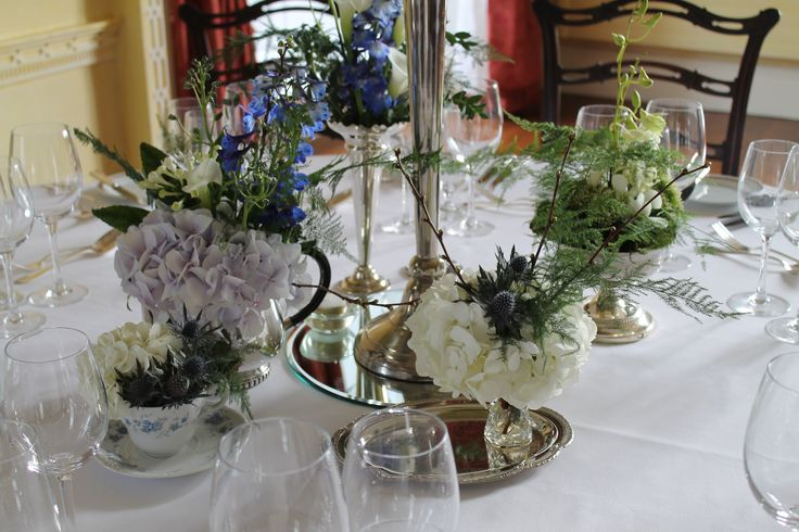 Silverwear plates and teapots filed with blue hydrangea and white bouvardia