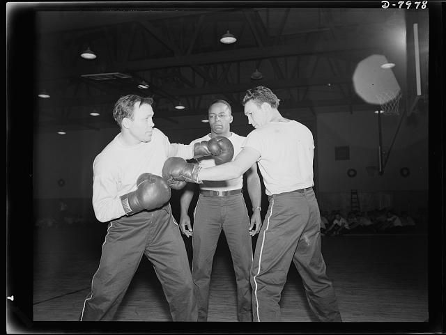 Manhattan Beach Coast Guard training station. Lou Ambers, former world's lightweight champion, sparring with Marty Servo, well-known pro, as Eristus Sams, former Tuskegee football and track star, referees. All three are boxing instructors at the Manhattan Beach Coast Guard training station