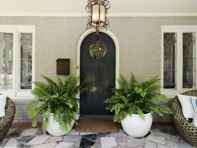 Tudor cottage in Dallas: a welcoming front door between potted ferns, and a beautiful front porch paved with color-matched gray & black flagstone...