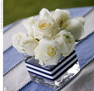 Square vases embellished with blue and white ribbon and filled with creamy white roses topped cocktail tables dressed in blue and white tablecloths. You can make these at home!
