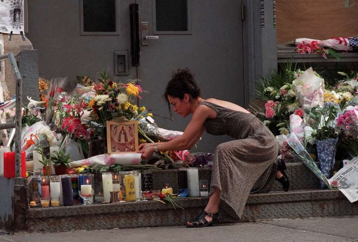 A woman places flowers and a religious picture on the doorstep of  John F. Kennedy Jr. and his wife Carolyn Bessette Kennedy's apartment Sunday, July 18, 1999, in New York.  Searchers looking for John F. Kennedy Jr.'s plane zeroed in on a spot at the bottom of the sea after picking up an automatic emergency signal Sunday, while Americans grieved over the almost certain deaths of Kennedy, his wife and her sister.(AP Photo/Louis Lanzano) Photo: LOUIS LANZANO, ASSOCIATED PRESS / AP1999