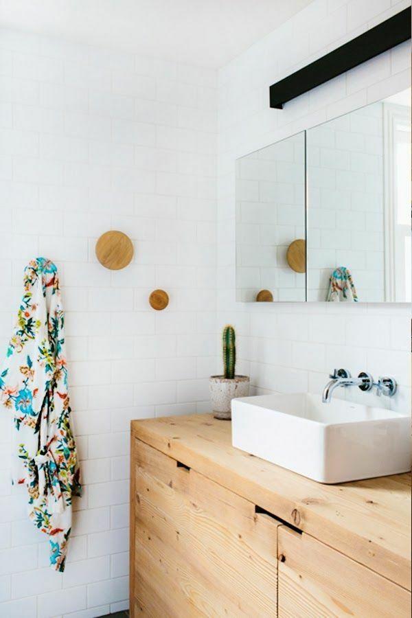 Une salle de bain très lumineuse avec petit meuble en bois clair