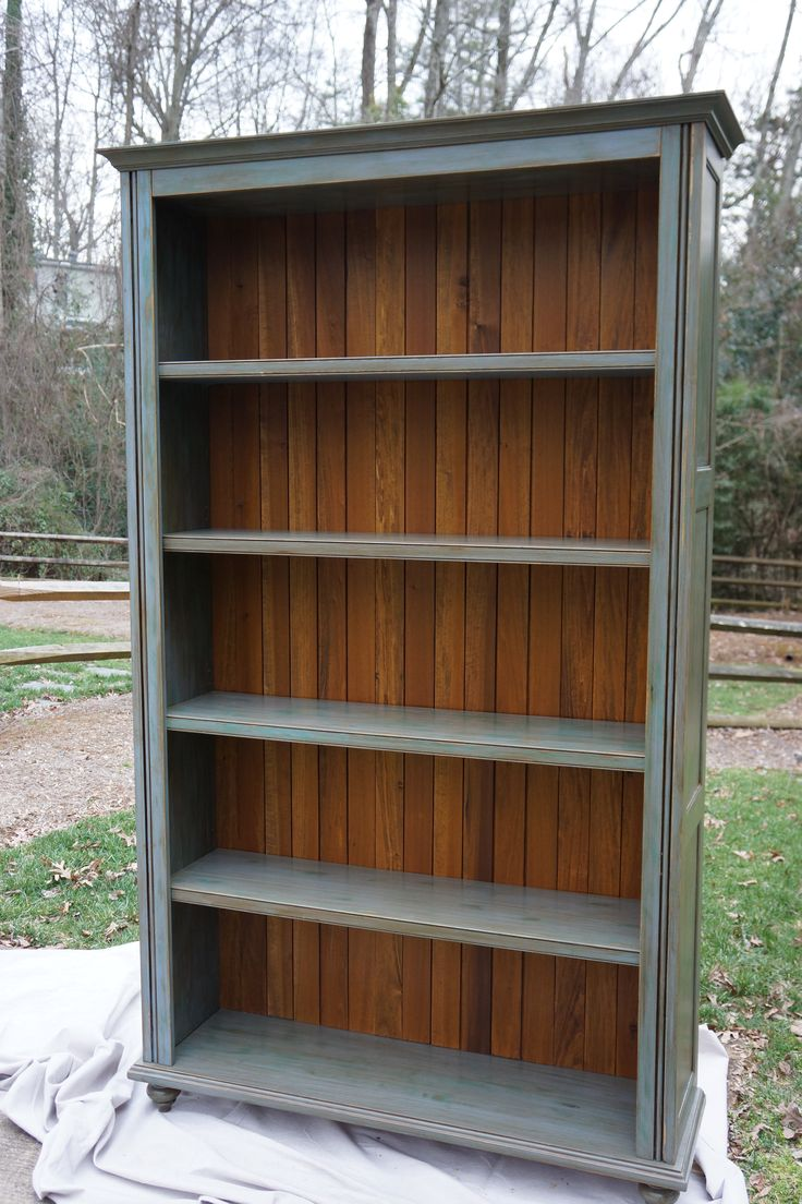 This 8' tall bookcase was custom-built in our shop. It features stained planks on the back, adjustable shelves with a subtle beaded face, flat-panel sides and a five-step hand-painted finish. While this piece is sturdy and built to last - it is designed to come apart easily which makes it much easier to move, if necessary.