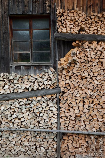 Wood is piled up on the side of a chalet in one of the hamlets near Saint Nicolas de Veroce, French Alps by Offrench