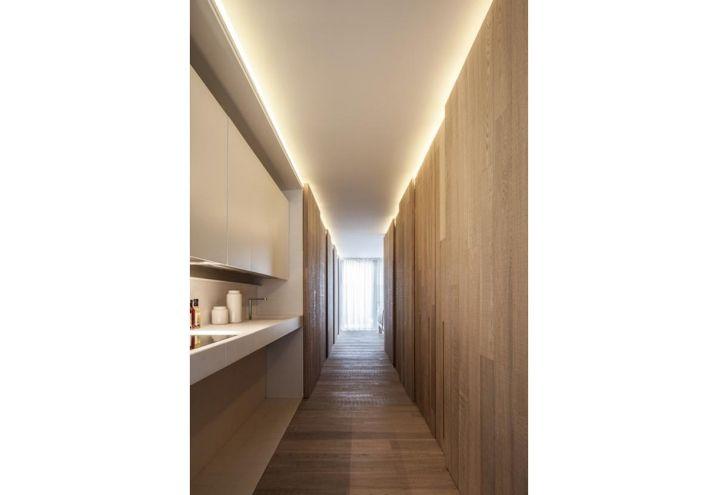 Il caldo corridoio rivestito in legno di quercia nel loft urbano di Bilzen ospita una nicchia con cucina su misura, che all'occorrenza viene celata da un pannello ribaltabile. Tutto è stato pensato da C.T. Architects per un utilizzo autonomo da parte del proprietario, costretto su una carrozzina