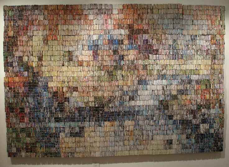"""Amanda Nelsen -- Book Artist and Binder """"Kinkade Recycled"""" (Mountain Retreat) This 8 by 5 foot wall hanging is comprised of approximately 40,000 pieces of junk mail, folded and string bundled into 2 inch cubes to create colored pixels."""