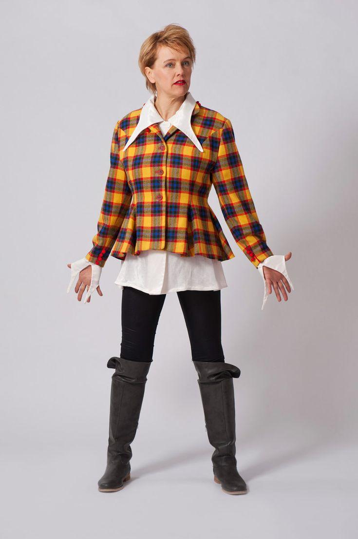 Gele wollen geruite jasje met rode pluchen bolletjes afgewerkt. Witte glanzende blouse met lang uitlopende kraag en manchetten.