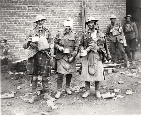 Wounded, but smiling soldiers enjoy a cup of soup after being treated. DEPARTMENT OF NATIONAL DEFENCE