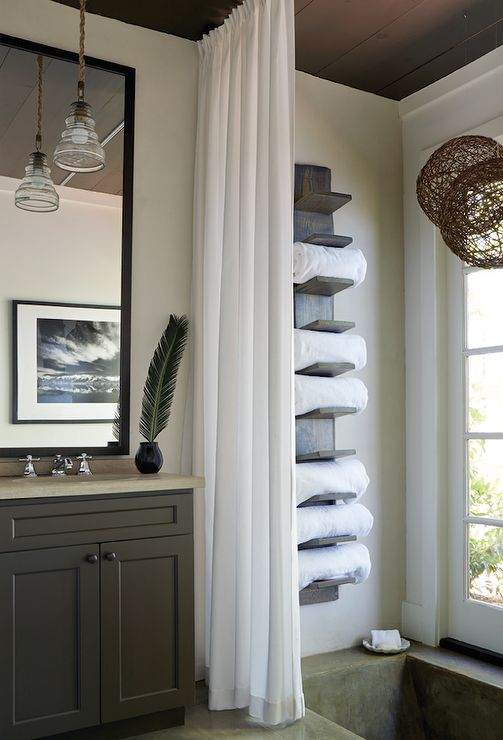 Cottage bathroom features a concrete in-ground tub placed under window and a vertical towel rack filled with fluffy white towels finished with a white shower curtain.