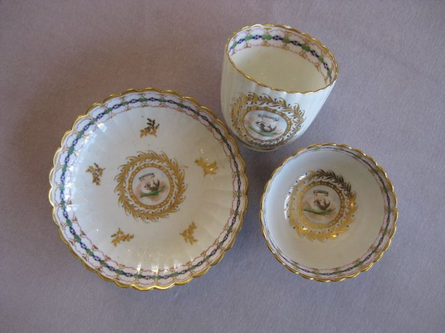 "A Caughley   fluted trio finely decorated with the ""L'amitie"" with two doves within a fancy gilt cartouche. Gilt and polychrome border  Unmarked  Circa  1790"