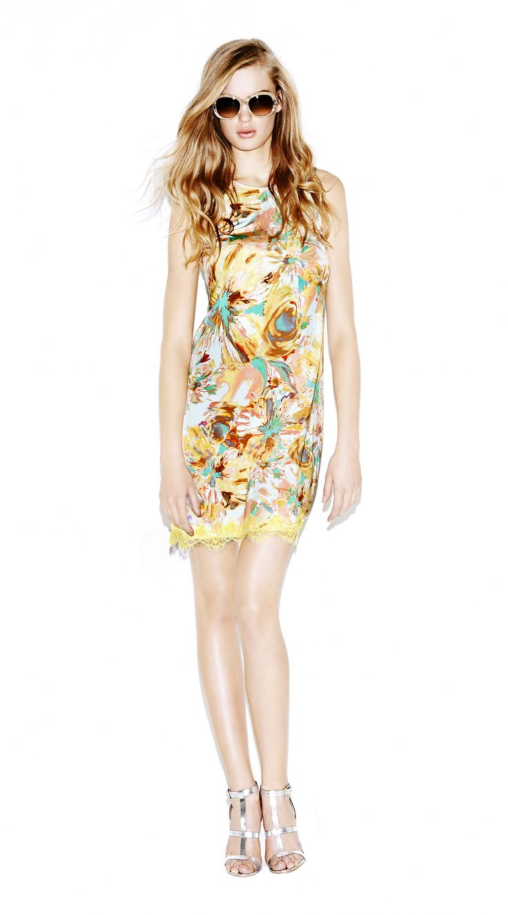 Model wears Naughty Dog flower print mini dress decorated with yellow lace applications.