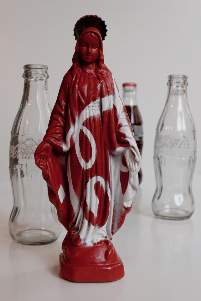 iDOLL - Alessandro D'Angeli e Ivo Caruso  Quanto sono diversi oggi la statuina della Madonna e la popolare bottiglia di CocaCola?