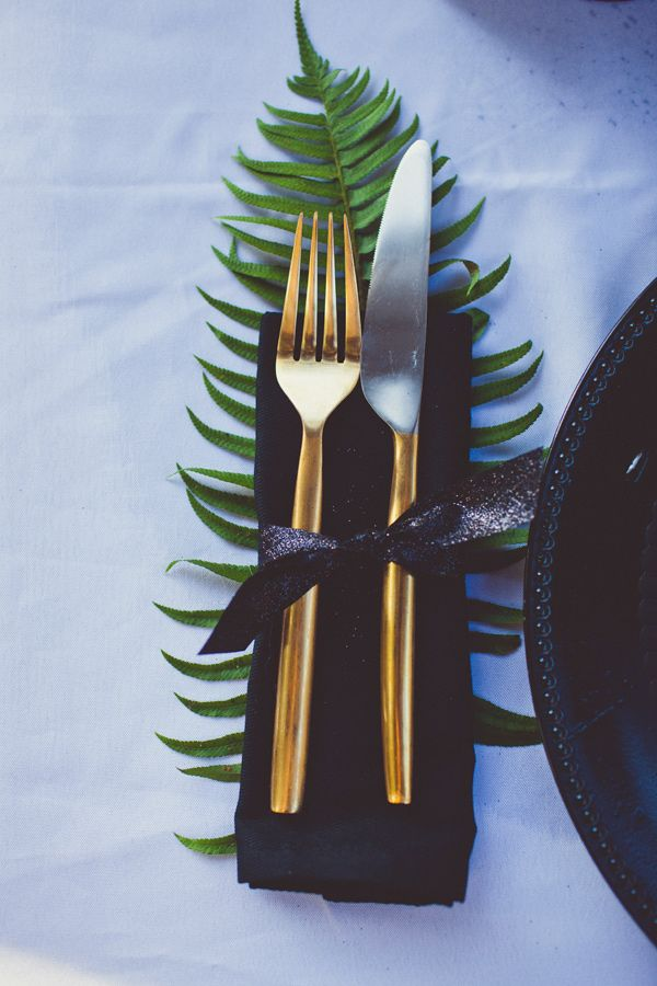 Golden utensils on top of contrasting black napkin with a fern - so elegant! #gold #goldwedding #goldweddingideas #weddingdecor #tablesetting