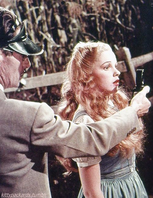 """Princess Dorothy."" On the first day of filming, Judy Garland, in her blonde wig and lacquered cosmetics, holds her mark as Technicolor cameraman Allen Davey takes a light meter reading just prior to shooting close-ups for the scene when Dorothy first encounters the Scarecrow, This is the only color photograph known to have survived from Richard Thorpe's tenure as director."