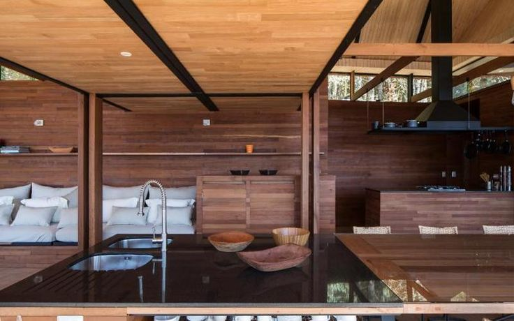 Living de Casa Quincho en Panguipulli de AB Estudio Arquitectos. Se aprecia el quincho integrado al living con zona de lavaplatos.