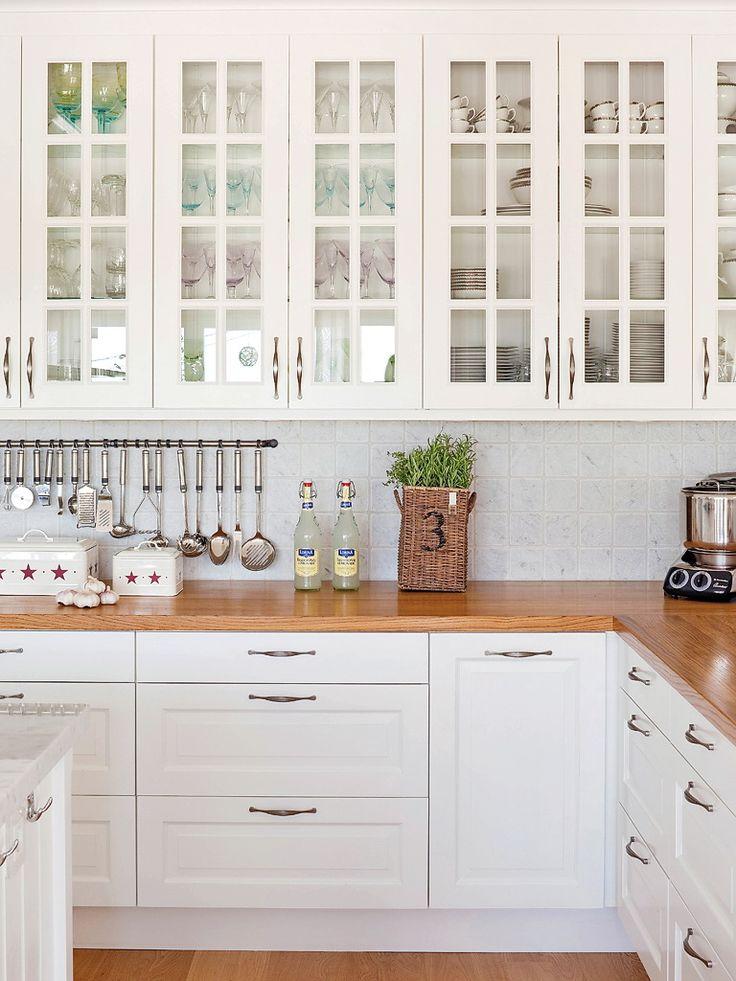 cocina con muebles en blanco encimera de madera y muebles altos con cuarterones de cristal