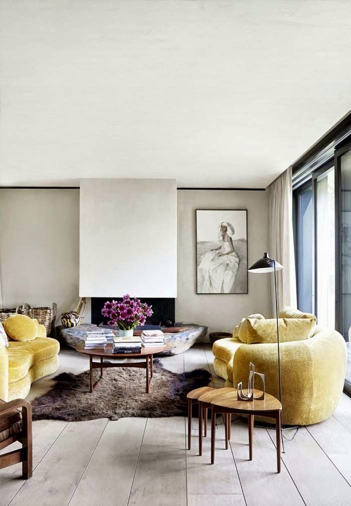 curvy mustard yellow velvet sofas, danish modern nesting tables, modern fireplace, wide plank flooring, modern floor lamp