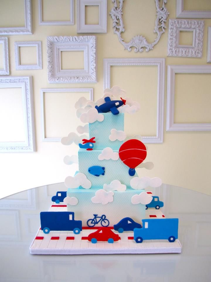 This four tier square children's cake is a blue cloud scene with airplanes, trucks, cars and balloons.  Airbrushed with blue, clouds added.