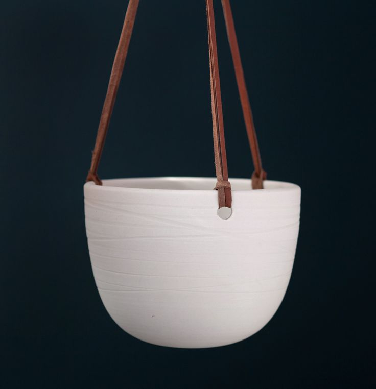 "A trio of 12"" long strands of leather lace suspend a porcelain bowl of contrasting smooth and rough textures. Choice of 4 deerskin leather strand colors; shown in saddle. Interior glazed in Bone. Cera"