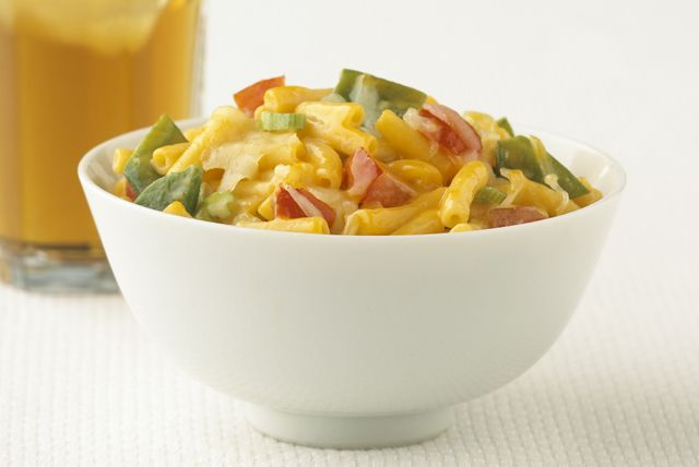 Colorful vegetables, including snow peas and chopped tomatoes, help add color and flavor to a quick weeknight mac and cheese dish.