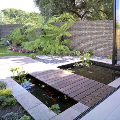 Flat wood bridge over small modern pond backyard for Modern garden pond designs