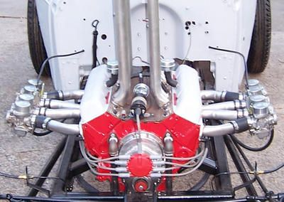 Reverse Flow Induction Small Block Chevy  Runs on E85 uses Flathead V8 Crab distributor (with original points), 2 racks of Honda 750 motorcycle carbs, remote water pump, and remote radiator - No external moving parts.