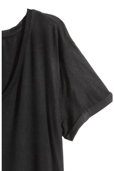 Top à encolure en V en jersey souple. Modèle à manches courtes avec revers cousu. Fentes latérales et un peu plus de longueur dans le dos.