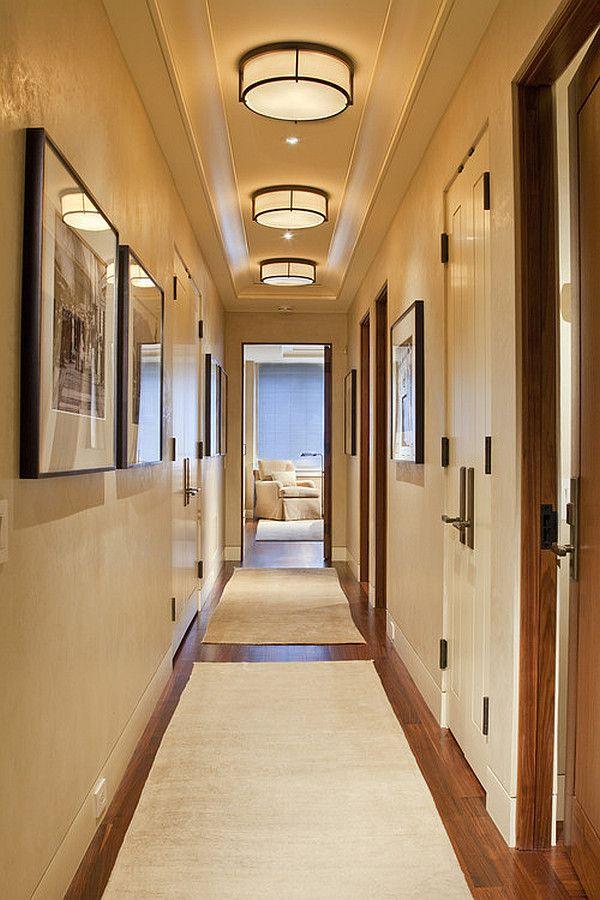 Long narrow hallway. Candeeiros, molduras, tapetes, chão, portas dos armários no mesmo tom da parede e não das restantes portas