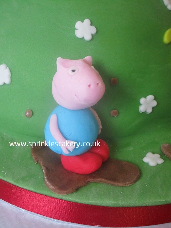 A handmade edible fondant George Pig jumping in a chocolate flavour muddy puddle.