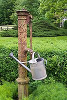 Watering can by old farm pump, irrigation in the garden, rustic antique, charming scene
