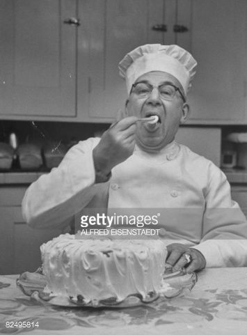 Stock Photo : Hearty pastry chef tasting the frosting